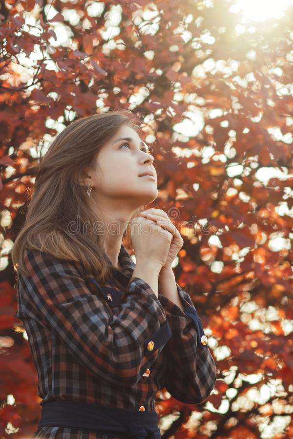 Portrait of a young woman praying in nature, the girl thanks God with her hands folded at her chin, a conversation with the stock images