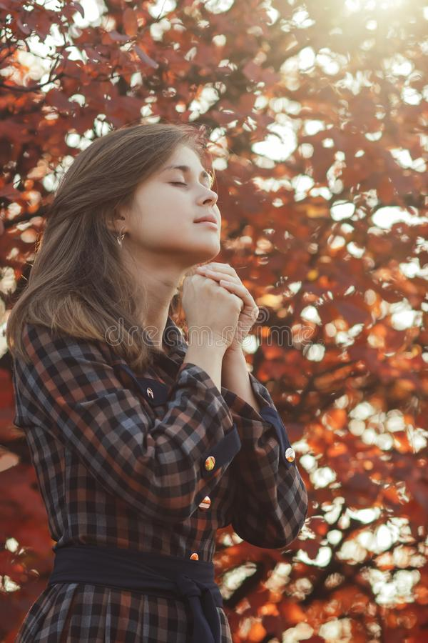Portrait of a young woman praying in nature, the girl thanks God with her hands folded at her chin, a conversation with the royalty free stock image