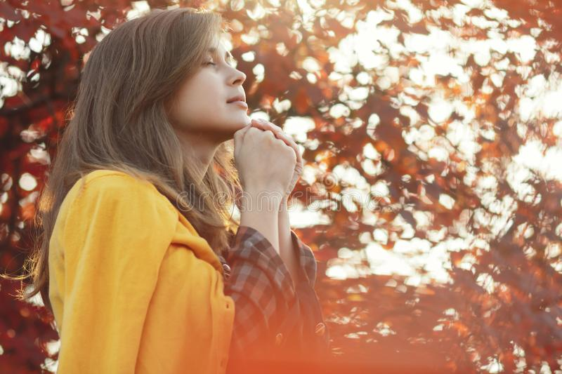 Portrait of a young woman praying in nature, the girl thanks God with her hands folded at her chin, a conversation with the stock image