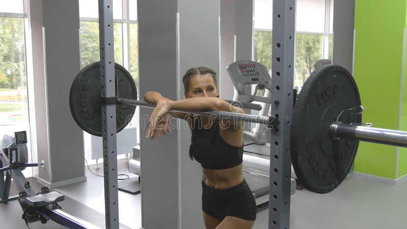 Portrait of young woman prepares to lift heavy barbells at the gym. Female athlete taking a barbell with heavy weights stock photos