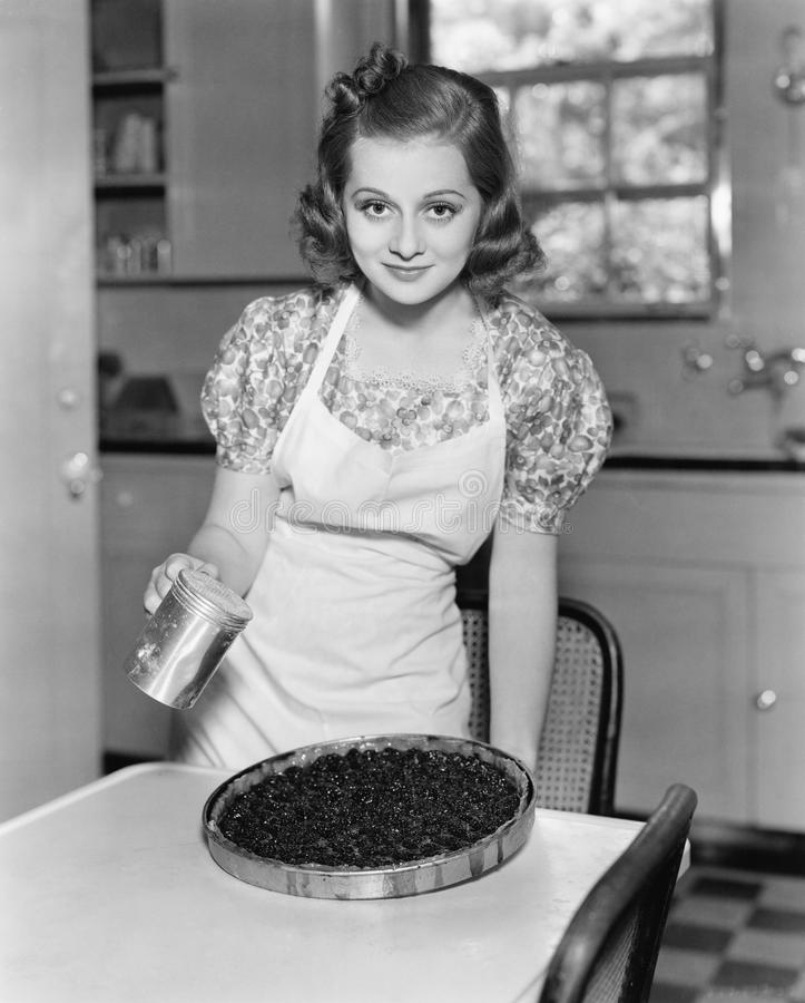 Portrait of a young woman preparing a blueberry pie in the kitchen stock photo