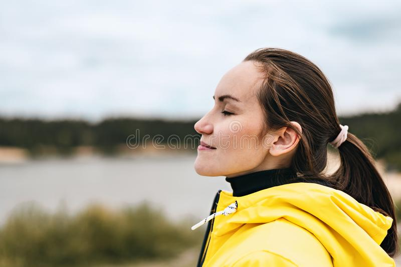 Portrait of a young woman in profile in nature breathing fresh, clean, cool air with copy space stock photography