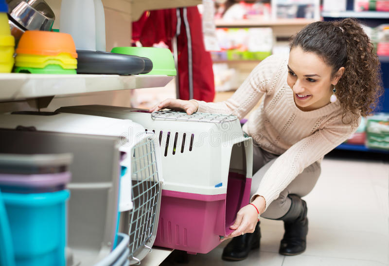 Portrait of young woman purchasing pet kennels stock images