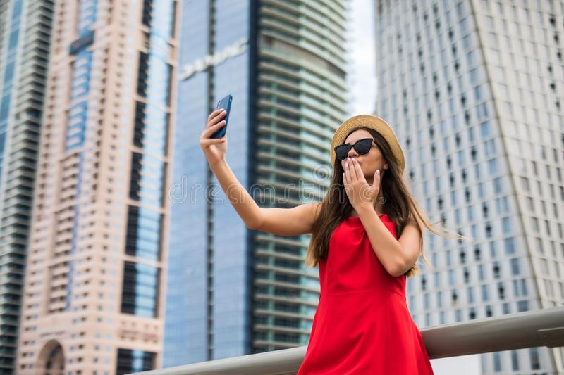 Portrait of young smile woman in red dress, sunglasses and summer hat make selfie or video call blow kiss on the phone on downtown royalty free stock image