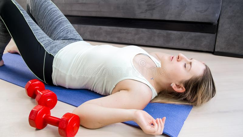 Portrait of young woman relaxing after sit-ups on floor stock image