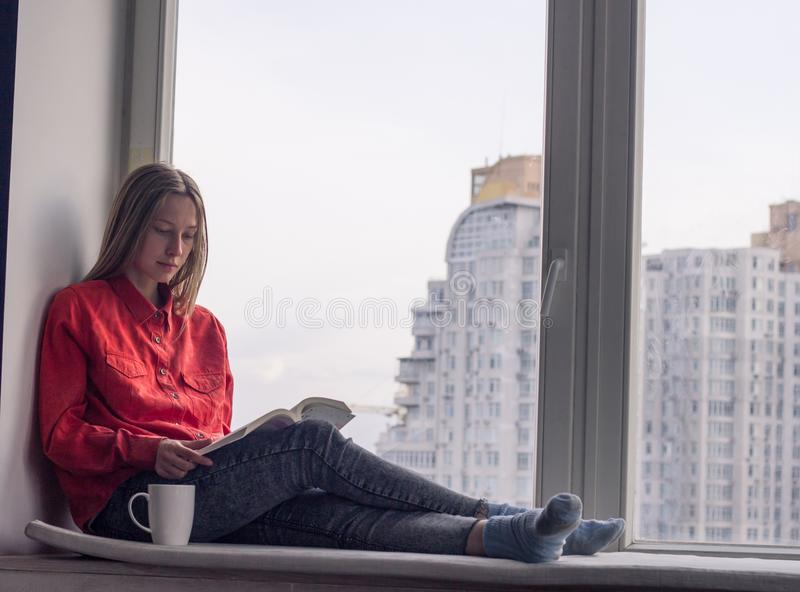 Young woman relzxing with book on window sill. Portrait of young woman relzxing with book and cup of coffee or tea on window sill stock images