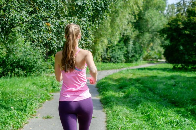 Portrait of a young woman running alone in the park stock photography