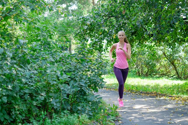 Portrait of a young woman running alone in the park royalty free stock image