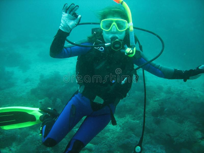 The portrait of young women scuba diver under water. She is in full scuba diving equipment: mask, regulator, BCD. She is showing O royalty free stock image