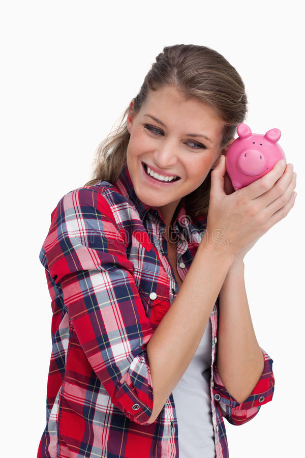 Portrait of a young woman shaking a piggy bank stock image