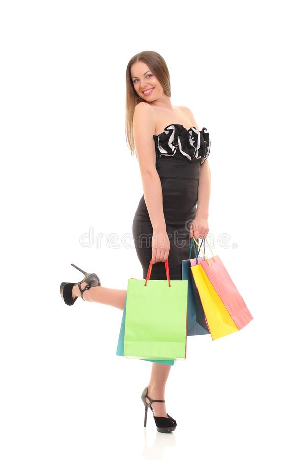 Portrait of young woman with shopping bags against white background royalty free stock images