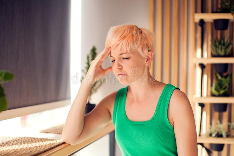 Portrait of young woman with short hair touching her temples feeling stress indoor. People, healthcare concept royalty free stock image