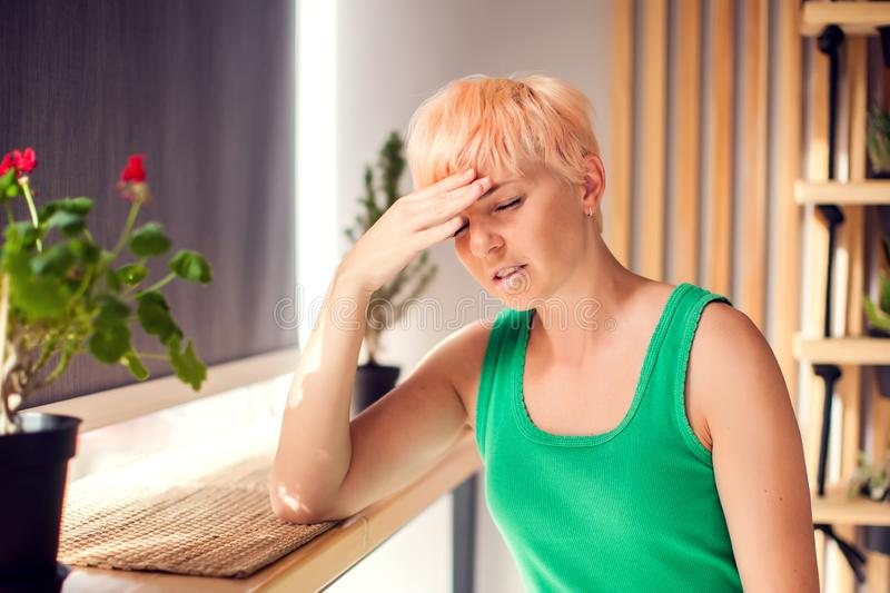 Portrait of young woman with short hair touching her temples feeling stress indoor. People, healthcare concept stock images