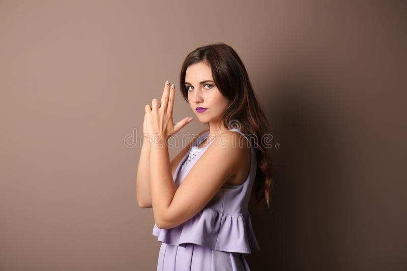 Portrait of young woman showing hand pistol gesture on color background stock image