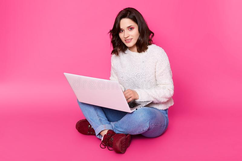 Portrait of young woman sits with legs crossed, uses laptop computer. Brunette female works online at home, earns money in stock photography
