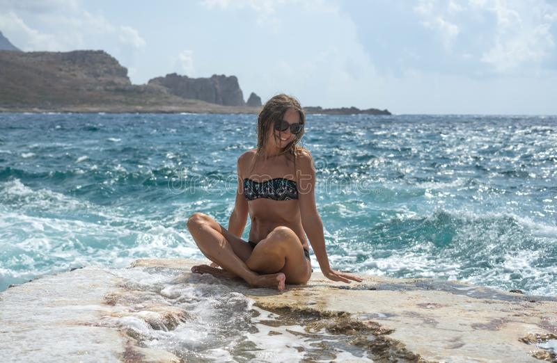 Portrait. Young woman sitting on a large rock and looks into the distance at sea. Selective soft focus. Happy summer days. Balos stock images