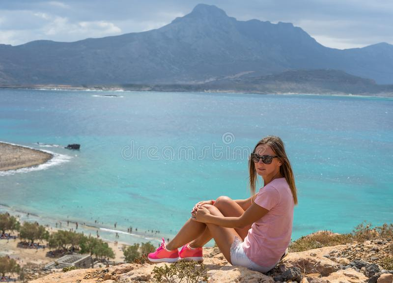 Portrait. Young woman sitting on a large rock and looks into the distance at sea. Selective soft focus. Happy summer days. Balos stock photography