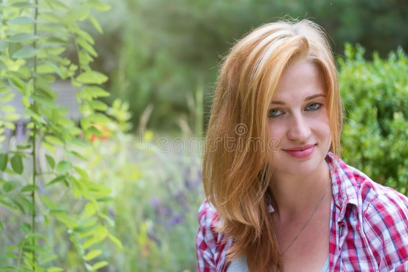 Portrait of young woman with slightly disheveled long hair. Smiling attractive young woman with slightly disheveled long hair is looking at the camera outdoors stock photos