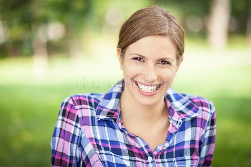 Portrait Of A Young woman smiling at the camera. At the park. stock images