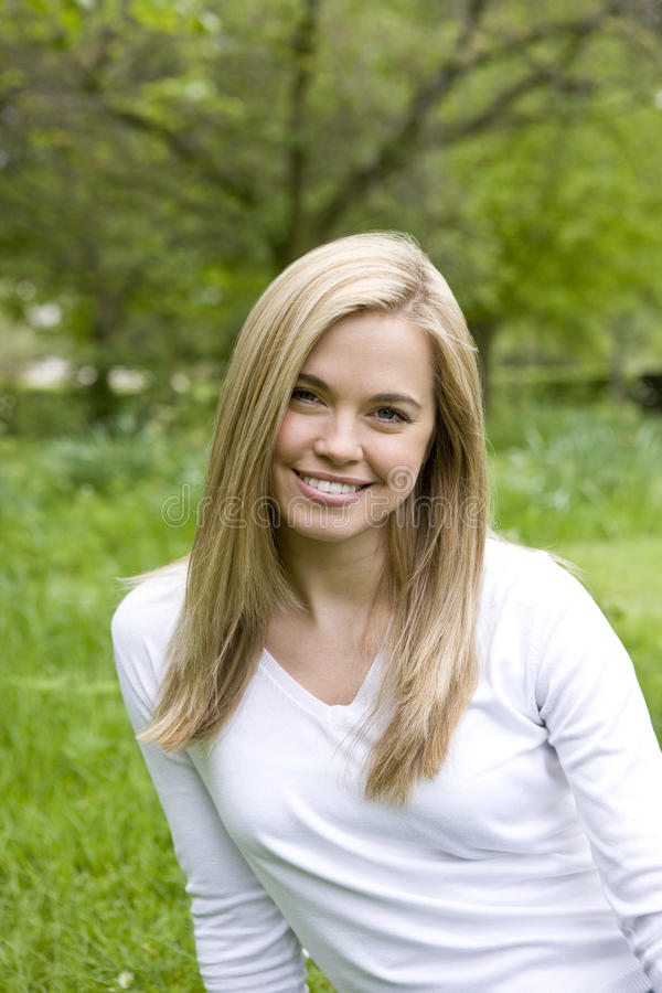 Portrait of a young woman smiling, sitting on the grass royalty free stock photo