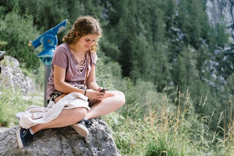 Portrait of young woman smiling and sitting in viewpoint in the royalty free stock photos