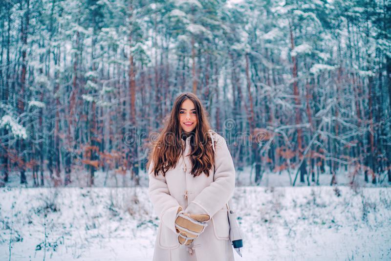 Portrait of a young woman in snow trying to warm herself. Joyful Beauty young woman Having Fun in Winter Park. royalty free stock images