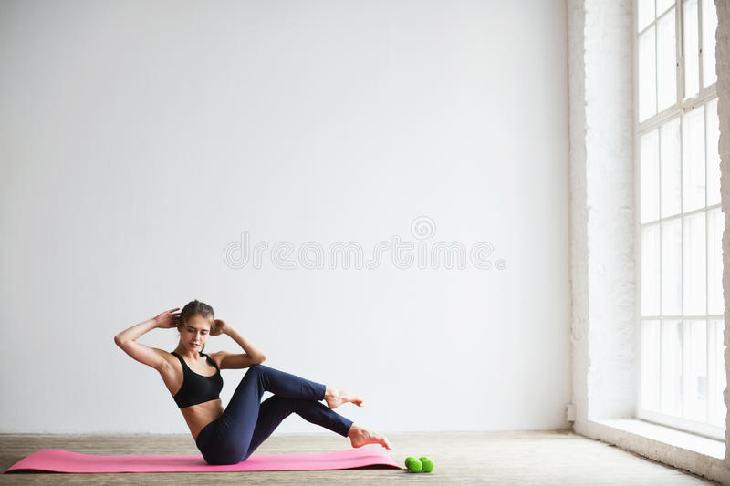 Portrait of young woman in sportswear, doing fitness exercise. stock photos