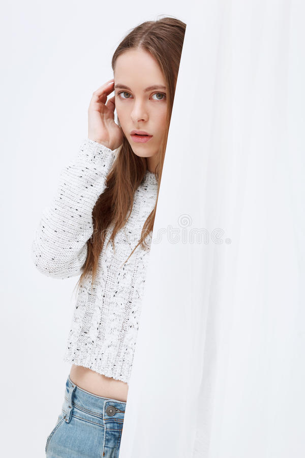Portrait of young woman standing against curtains. stock photos