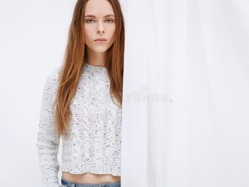 Portrait of young woman standing against curtains. stock photography
