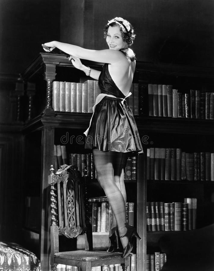 Portrait of a young woman standing on a chair and dusting a bookshelf in a outfit stock images