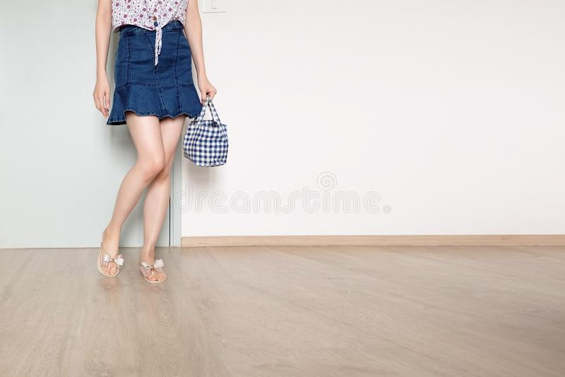 Portrait Young Woman is Standing. Fashion Model Female is Holding Blue Bag. Girl in a Blue Jeans Dress and Bow Shoes At Home stock photo