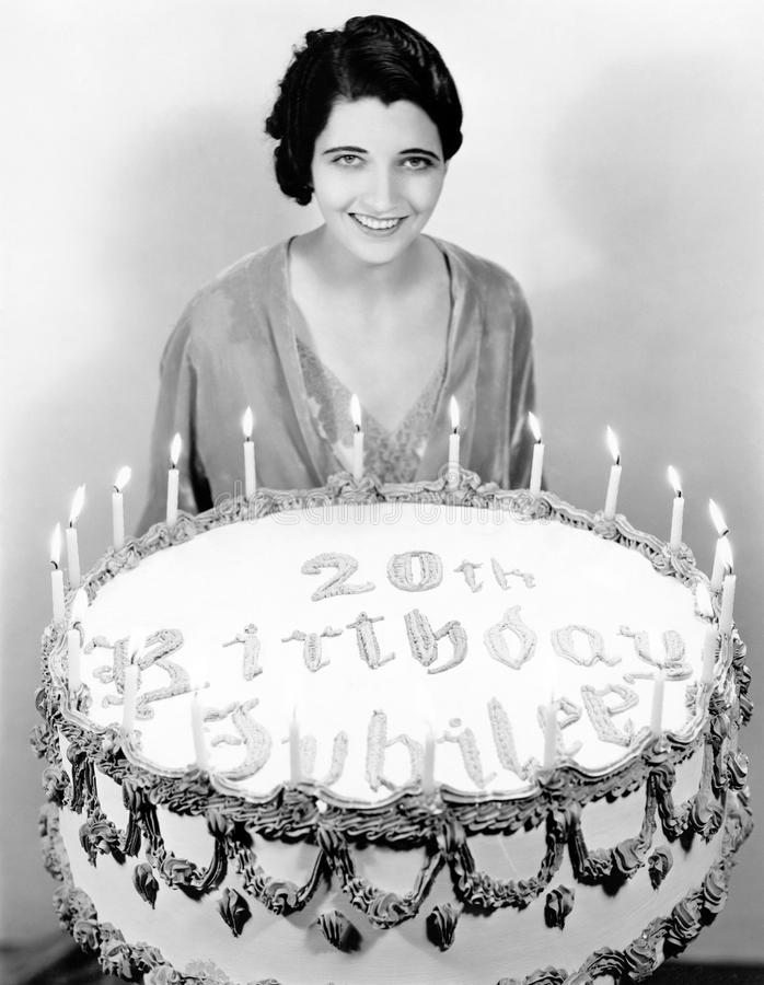 Portrait of a young woman standing in front of a birthday cake. (All persons depicted are no longer living and no estate exists. Supplier grants that there will royalty free stock photos