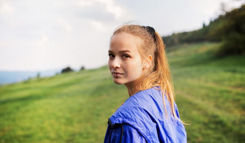 A portrait of young woman standing in nature, looking back. royalty free stock photos