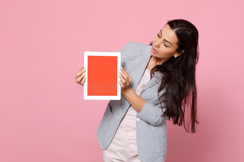 Portrait of young woman in striped jacket hold, looking on tablet pc computer with blank empty screen isolated on pink stock image