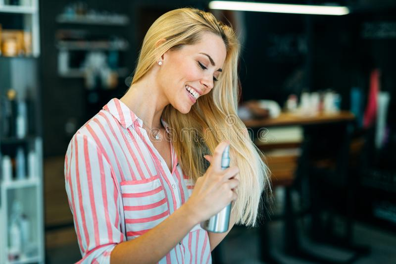 Portrait of a young woman styling her hair with spray. Portrait of a cute young woman styling her hair with spray stock image