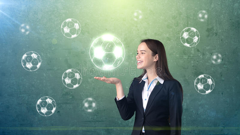 Portrait of young woman in suit holding soccer ball on the open hand palm, drawn studio background. Business concept. stock photography