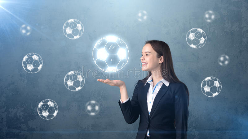 Portrait of young woman in suit holding soccer ball on the open hand palm, drawn studio background. Business concept. stock photos