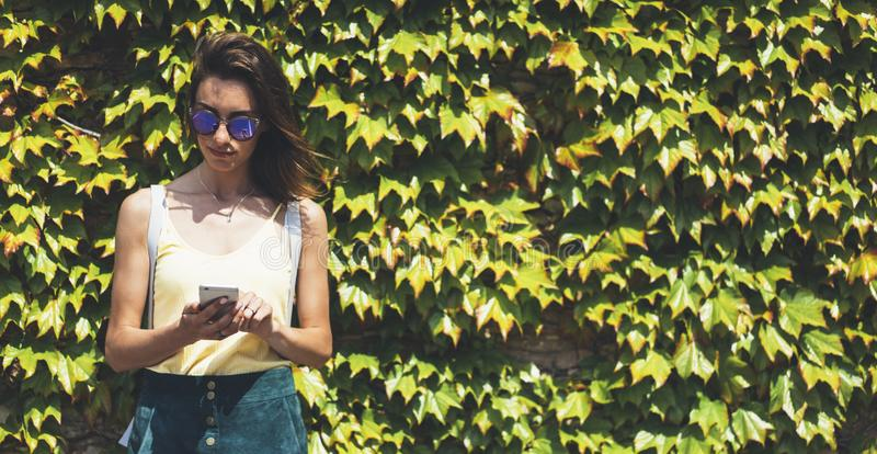 Portrait young women in sunglasses using smart phone isolated on background green nature wall mock up, pretty hipster female hands royalty free stock photo