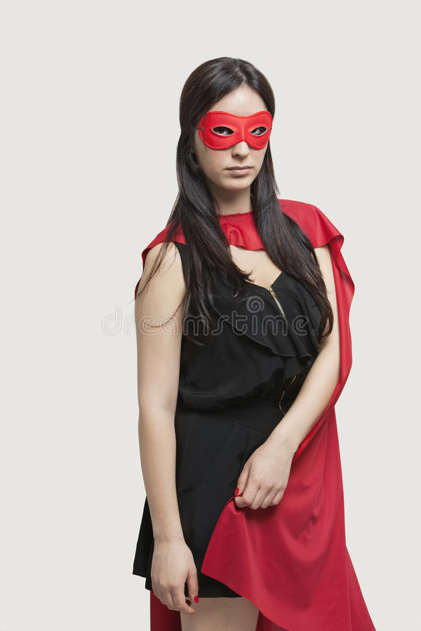 Portrait of young woman in superhero costume standing against gray background royalty free stock images