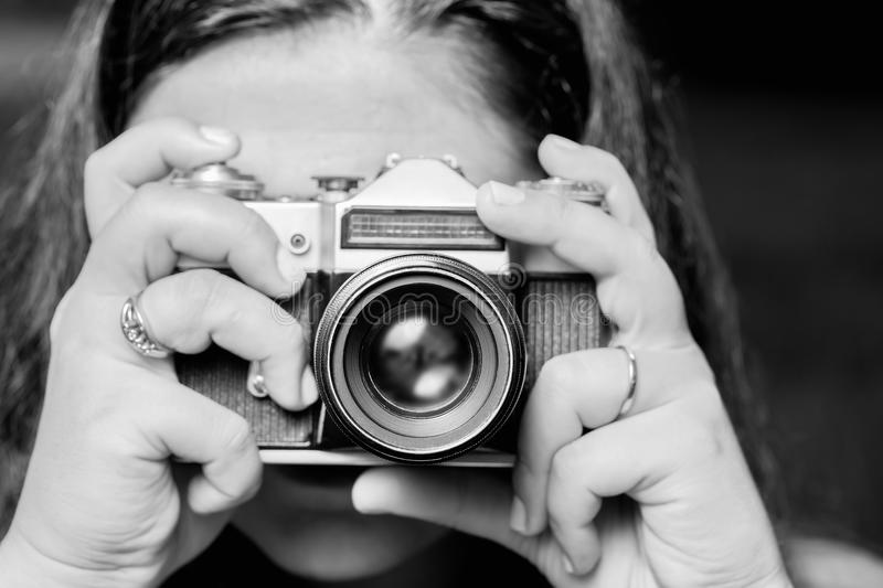 Portrait of young woman taking photos with vintage retro camera. Black and white.  stock image