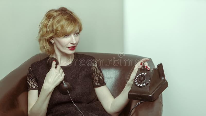 Portrait of young woman talking using a vintage telephone agains stock photo