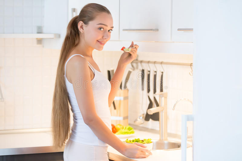 Portrait of a young woman tasting a green salad on the kitchen,. Young woman with long braid standing at the kitchen and trying green salad, wearing underwear royalty free stock photography
