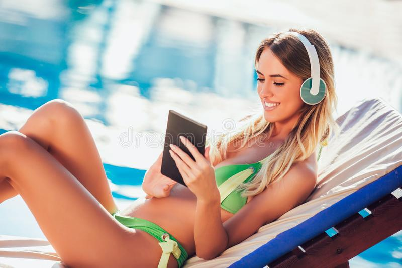 Portrait of young woman in the tropical sun near swimming pool. On a deck chair using digital tablet stock photo