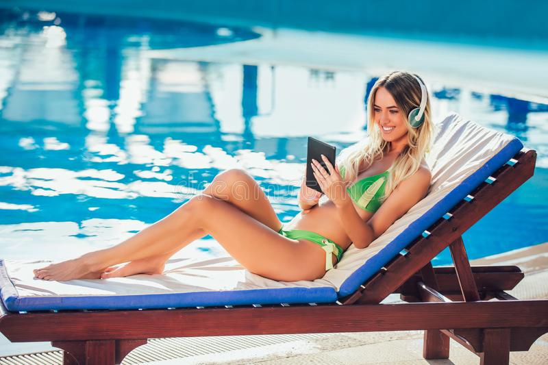 Portrait of young woman in the tropical sun near swimming pool. On a deck chair using digital tablet stock photos