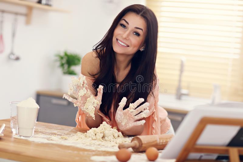 Young woman trying to make pierogi in kitchen stock photos