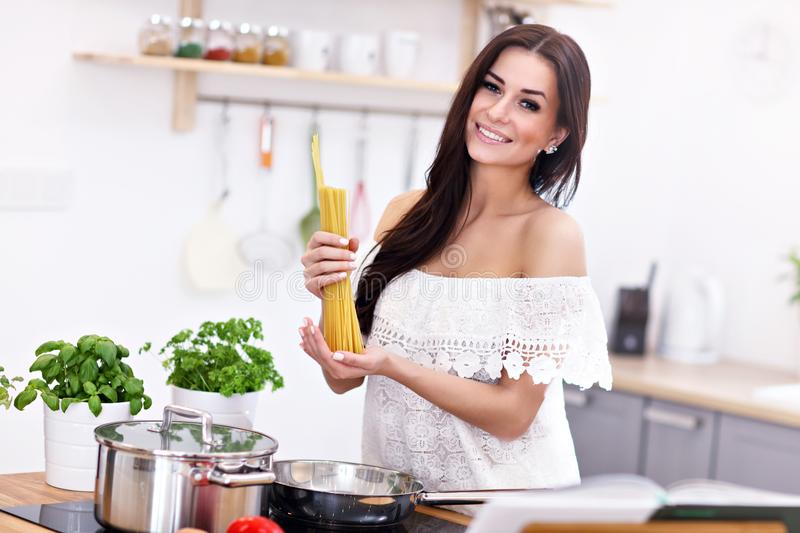 Young woman trying to prepare pasta in kitchen stock images