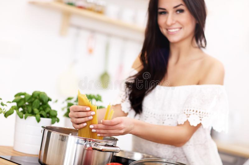 Young woman trying to prepare pasta in kitchen stock photo
