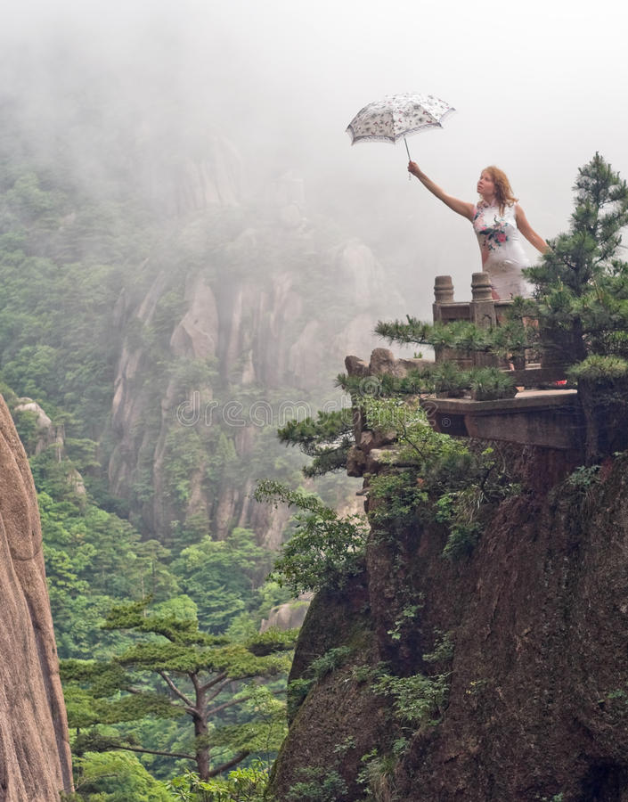 Portrait of young woman with umbrella at cloudy weather. Portrait image of young woman with umbrella at cloudy weather on top of the Chinese mountain of royalty free stock image