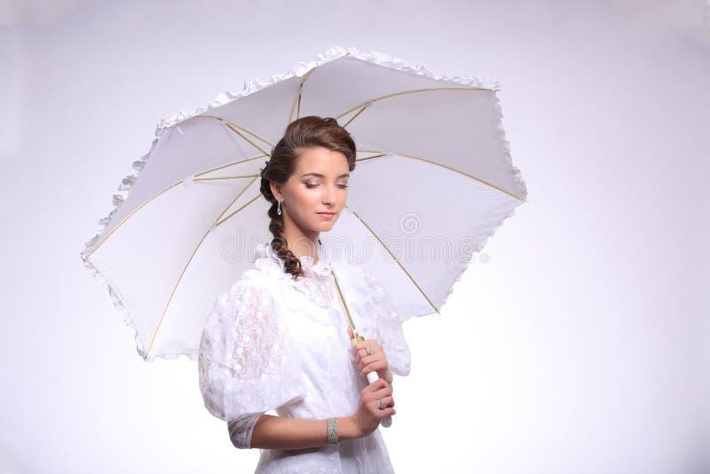 Portrait of young woman with umbrella retro wedding. Studio royalty free stock image