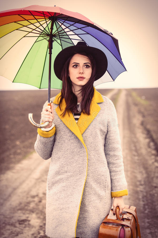 Portrait of a young woman with umbrella and suitcase royalty free stock image